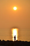 Nascer do sol com um pescador e uma barca pequena no horizonte, Caorle, Itália Imagens de Stock Royalty Free