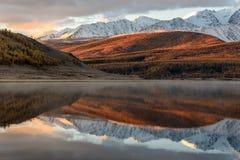 Nascer do sol da neve da reflexão das montanhas do lago Fotos de Stock