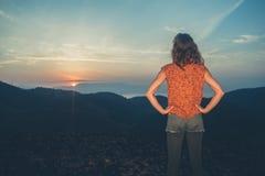 Nascer do sol de observação da mulher sobre montanhas Fotografia de Stock