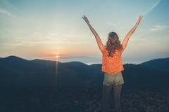 Nascer do sol de observação da mulher sobre montanhas Imagem de Stock