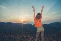 Nascer do sol de observação da mulher sobre montanhas Fotos de Stock