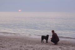 Nascer do sol de observação do homem e do cão Fotos de Stock Royalty Free
