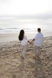 Nascer do sol de observação dos pares latino-americanos românticos na praia Foto de Stock