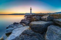 Nascer do sol do farol do grande lago com rochas Imagens de Stock Royalty Free