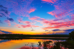 Nascer do sol do por do sol com nuvens, raios claros e o outro efeito atmosférico, equilíbrio branco seletivo Fotografia de Stock Royalty Free