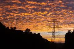 Nascer do sol dramático em um dia novo que ilumina-se acima das linhas elétricas elétricas imagem de stock royalty free