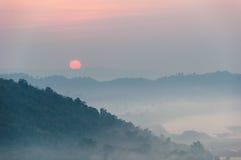 Nascer do sol e névoa na paisagem da montanha Imagem de Stock