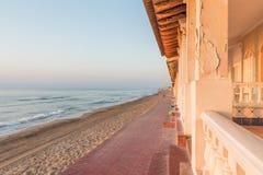 Nascer do sol em casas velhas na frente marítima de uma praia mediterrânea Imagem de Stock