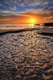Nascer do sol em uma praia Fotografia de Stock Royalty Free