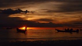 Nascer do sol em uma praia tropical silhuetas dos barcos e os povos, a areia e o mar vídeos de arquivo