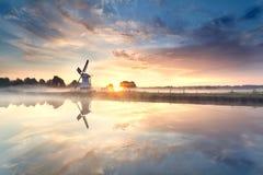 Nascer do sol enevoado sobre o moinho de vento pelo rio fotografia de stock royalty free
