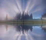 Nascer do sol enevoado surpreendente sobre o lago da floresta carpathian Fotografia de Stock Royalty Free