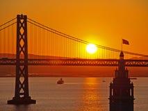 Nascer do sol entre o edifício da balsa & a ponte do louro Fotos de Stock Royalty Free