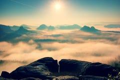 Nascer do sol fantástico na parte superior da montanha rochosa com a vista no vale enevoado fotografia de stock royalty free
