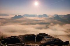 Nascer do sol fantástico na parte superior da montanha rochosa com a vista no vale enevoado foto de stock
