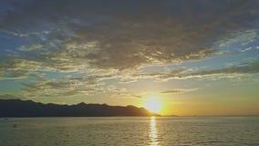Nascer do sol fantástico sobre o oceano contra montes sob o céu vídeos de arquivo