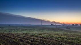 Nascer do sol impressionante sobre um campo com um moinho de vento no outono, timelapse video estoque