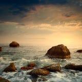 Nascer do sol na costa de mar rochosa Imagens de Stock