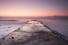 Nascer do sol na costa rochosa do Mar Negro com cais velho fotos de stock royalty free