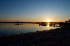 Nascer do sol na doca no rio Fotografia de Stock Royalty Free