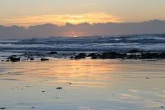 Nascer do sol na maré baixa na baía Londres do leste de Morgan na costa selvagem de África do Sul fotografia de stock