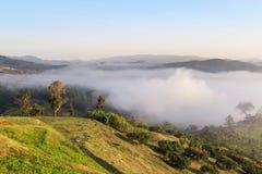 Nascer do sol na opinião de ângulo alto com névoa branca na manhã sobre a montanha da floresta úmida em Tailândia Foto de Stock