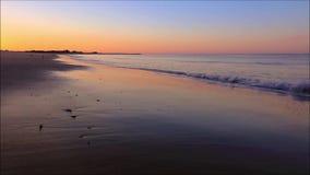 Nascer do sol na praia como a maré baixa se move delicadamente dentro e para fora video estoque