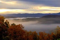Nascer do sol na via pública larga e urbanizada ocidental, montanhas fumarentos dos montes, TN EUA. Foto de Stock