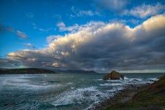 Nascer do sol nebuloso na costa rochosa Foto de Stock Royalty Free