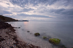 Nascer do sol nebuloso na costa rochosa do Mar Negro fotografia de stock
