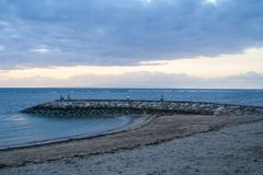 Nascer do sol nebuloso na praia em Sanur, Bali foto de stock royalty free