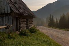 Nascer do sol nevoento na aldeia da montanha velha pequena fotografia de stock