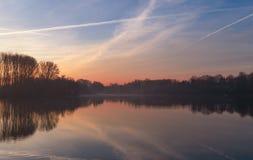 Nascer do sol nevoento sobre o lago imagem de stock