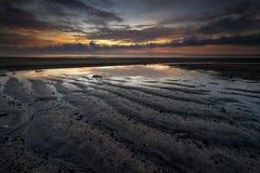 Nascer do sol do oceano quando maré baixa e lata para ver o teste padrão da areia imagem de stock royalty free