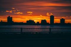 Nascer do sol do por do sol atrás das construções da cidade fotografia de stock