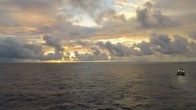 Nascer do sol a pouca distância do mar do lapso de tempo com operação do barco do grupo e nuvem movente para o monitor filme