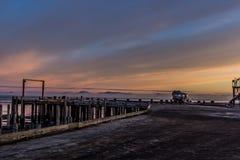 Nascer do sol sobre Bristol Bay da doca em Ekuk Alaska na maré baixa fotos de stock
