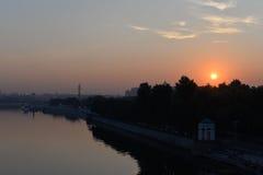 Nascer do sol sobre a cidade e o rio Imagens de Stock
