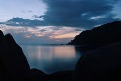 Nascer do sol sobre espelho-como a superfície do mar atrás das pedras Foto de Stock Royalty Free