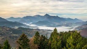 Nascer do sol sobre a floresta no lapso, nas nuvens e nas árvores de tempo das montanhas do outono movendo-se no vento vídeos de arquivo