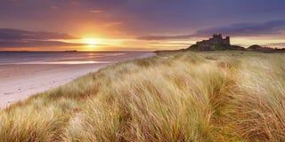 Nascer do sol sobre o castelo de Bamburgh, Northumberland, Inglaterra imagens de stock