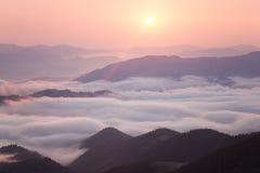 Nascer do sol sobre o cume nebuloso da montanha foto de stock