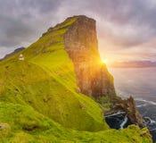 Nascer do sol sobre o farol da ilha e do Kallur de Kalsoy, Ilhas Faroé Fotografia de Stock