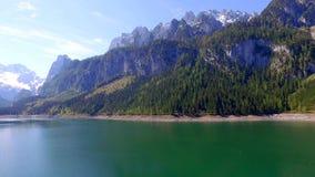Nascer do sol sobre o lago da montanha em Gosau em Áustria, cumes vídeos de arquivo