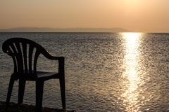 Nascer do sol sobre o mar e uma cadeira na praia Fotos de Stock