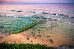 Nascer do sol sobre o oceano Cais de pedra velho coberto de vegetação com as algas Austrália, NSW, Newcastle imagens de stock