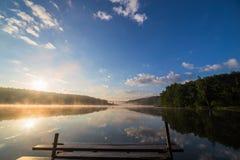 Nascer do sol sobre o rio nevoento com um cais de madeira foto de stock