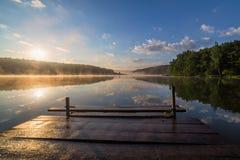 Nascer do sol sobre o rio nevoento com um cais de madeira imagem de stock royalty free