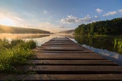 Nascer do sol sobre o rio nevoento com um cais de madeira foto de stock royalty free