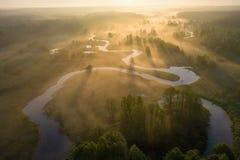 Nascer do sol sobre o rio nevoento de cima de Raios de sol brilhantes no rio enevoado no prado Opinião aérea da natureza do verão imagens de stock royalty free